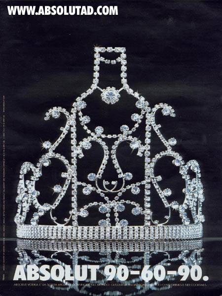 The tiara is resting on a reflective surface against a black background