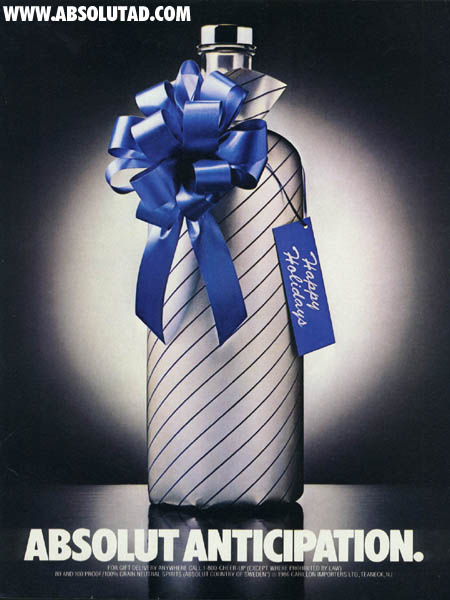 Bottle in silver wrapping paper with blue label on it.