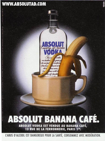 Bottle with a coffee cup in front of it that has a banana in it.